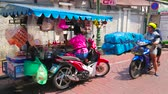 khaosan : BANGKOK, THAILAND - APRIL 22, 2019: The street vendor of beverages makes coffee for the client, sitting at the motorcycle cart in Banglampoo district, on April 22 in Bangkok