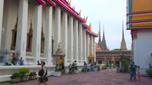 Чеди : BANGKOK, THAILAND - APRIL 22, 2019: People walk along the Phra Rabiang cloister to the Phra Ubosot (main temple) of Wat Pho, on April 22 in Bangkok Стоковые видеозаписи