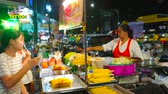 khaosan : BANGKOK, THAILAND - APRIL 22, 2019: The street food vendor offers grilled corn and traditional Thai noodles in Night market along the Charkrapong Road, Banglampoo, on April 22 in Bangkok