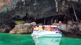 gruta : PHIPHI LEH, THAILAND - APRIL 27, 2019: Panorama of the Viking Cave (Tham Phaya Nak) with a tourist speed-boat, making Phi Phi Island tour, on April 27 in PhiPhi Leh