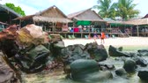 rif : PHUKET, THAILAND - MAY 1, 2019: The view from the beach on the lounge zone of Khai Nai island, consisting of stilt huts, serving as cafes, souvenir shops and covered terraces, on May 1 on Phuket Stockvideo