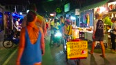 stragan : PAI, THAILAND - MAY 5, 2019: The crowded Night Market in Walking Street with many food and souvenir stalls, cafes, bars; the street vendor with cart offers home made coconut ice cream, on May 5 in Pai Wideo