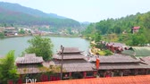 禁止 : BAN RAK THAI, THAILAND - MAY 6, 2019: Panorama of Mae Aw tea village from hill, observing sweeping Chinese roofs of tea houses, small cottages and Mae Sa-Nga lake, on May 6 in Ban Rak Thai, Thailand