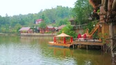 禁止 : The bank of Mae Sa-Nga lake with a view on green hills, small cottages and Chinese style wooden boat, decorated with red lanterns, moored at the pier, Ban Rak Thai village (Mae Aw), Thailand