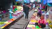 禁止 : MAEKLONG, THAILAND - MAY 13, 2019: The tourists and visitors walk along the railroad of Maeklong Railway Market, make pictures and choose fresh fruits and other foods, on May 13 in Maeklong 動画素材