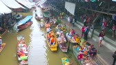 retailers : DAMNOEN SADUAK, THAILAND - MAY 13, 2019: Chaotic boat traffic along klong (canal) of Ton Khem department of floating market with souvenirs, snacks, fruits and other goods, on May 13 in Damnoen Saduak
