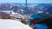 on piste : Observe the snowy Zwolferhorn mountain slope, turquoise surface of Wolfgangsee lake and Alpine peaks around it from swaying cable car gondola, riding to mountain top, St Gilden, Salzkammergut, Austria