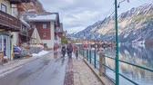 сувенир : HALLSTATT, AUSTRIA - FEBRUARY 25, 2019: Pleasant walk along embankment of Hallstatt with a view on line of traditional houses, old port, Hallstattersee lake and snowy Alps, on February 25 in Hallstatt