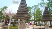 pavilion : CHIANG RAI, THAILAND - MAY 9, 2019: The carved shrine and prayer trees with numerous metal bo (pho, bodhi) silver leaves, located on the grounds of White Temple (Wat Rongkhun), on May 9 in Chiang Rai Stock Footage