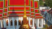 Чеди : The view from the top of Loha Prasat shrine on golden stupa with relief pattern, lacelike umbrella and the image house of Wat Ratchanatdaram Temple with colorful gable roof, Bangkok, Thailand