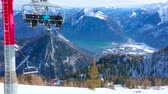 pista da sci : EBENSEE, AUSTRIA - FEBRUARY 24, 2019: The chairlift, carrying sportsmen to the top of Feuerkogel mount with a view on Traunsee lake valley amid rocky snowy Dachstein Alps, on february 24 in Ebensee Filmati Stock