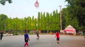 basketball : CHIANG MAI, THAILAND - MAY 4, 2019: People play local street game - mix of Thai sepak takraw and basketball with one basket, hanging from above amid the field, Buak Hard Park, on May 4 in Chiang Mai Stock Footage