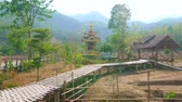 deshidratado : Walk through the curved Boon Ko Ku So bamboo bridge with shady pavilions, Buddhist shrine and dry agricultural lands around it, on May 5 in Pai Archivo de Video