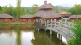 pavilion : Walk along the scenic pond with wooden bridge and watch traditional houses of Santichon Chinese Yunnan cultural village, located in mountains next to Pai, Thailand Stock Footage