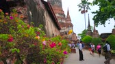 Аюттхая : AYUTTHAYA, THAILAND - MAY 5, 2019: The crowded alley in scenic garden on grounds of Wat Yai Chai Mongkhon complex with preserved Ubosot, chedis and shrines, on May 5 in Ayutthaya