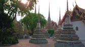 cerâmico : BANGKOK, THAILAND - APRIL 22, 2019: The pleasant evening walk among the ornate chedies of Wat Pho temple, enjoying magnificent architecture of famous religion complex, on April 22 in Bangkok