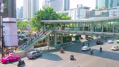 délkelet Ázsia : BANGKOK, THAILAND - APRIL 24, 2019: The busy Ratchadamri Road with  business centers, skyscrapers, malls and skywalk, on April 24 in Bangkok Stock mozgókép