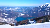 on piste : The view from the top of snowy Zwolferhorn mount on valley of Wolfgangsee lake, colored gondolas of cable car and Alpine landscape of Salzkammergut, St Gilden, Austria