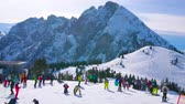 chairlift : GOSAU, AUSTRIA - FEBRUARY 26, 2019: The numerous skiers and boarders on top of Zwieselalm mount, overlooking sharp peaks of Dachstein West Alps, on February 26 in Gosau. Stock Footage