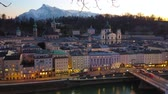 conservar : Watch the old town on sunset with silhouette of rocky Alps on background, illuminated embankment of Salzach river and churches domes, rising over the roofs, Salzburg, Austria Stock Footage