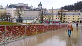プロテスタント : SALZBURG, AUSTRIA - MARCH 1, 2019: Pedestrians walk along the Makartsteg, decorated with numerous colored love locks on rainy weather, on March 1 in Salzburg 動画素材