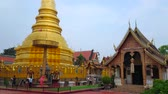 lanna : LAMPHUN, THAILAND - MAY 8, 2019: Devotees at Lanna style Phra Maha That golden Chedi with Chatra parasol next to Viharn (hall) Phra Chao Lawo of Wat Phra That Hariphunchai Temple, on May 8 in Lamphun