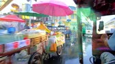 khaosan : BANGKOK, THAILAND - MAY 15, 2019: Tuk tuk drives through the rainy streets of Banglampoo neighborhood with wet buildings, people, hiding under umbrellas and busy Khaosan Road, on May 15 in Bangkok Stock Footage