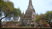 Аюттхая : AYUTTHAYA, THAILAND - MAY 14, 2019: Panorama of Wat Phra Si Sanphet archaeological site with chedis and ancient buildings foundations through the green trees, on May 14 in Ayutthaya