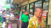 potato dishes : BANGKOK, THAILAND - MAY 15, 2019: The narrow busy sidewalk of Charoen Krung road in Chinatown with many stores and street stall, offering grilled bananas and sweet potato, on May 15 in Bangkok