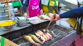 buurt : BANGKOK, THAILAND - APRIL 23, 2019: The  cooks make fish, octopuses and shrimps on grill in open air kitchen of cafe in Yaowarat road, Chinatown, on April 23 in Bangkok