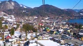 hava : ST GILGEN, AUSTRIA - FEBRUARY 23, 2019: The birds eye view of the tourist town, lower air lift station, Wolfgangsee lake and Inner Salzkammergut Alps on background, on February 23 in St Gilgen Stok Video