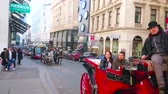 tranvía : VIENNA, AUSTRIA - FEBRUARY 18, 2019: The horse drawn carriages are popular tourist transport in old town, riding slow among the main landmarks through the crowded streets, on February 18 in Vienna. Archivo de Video