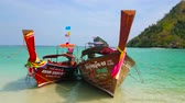 tropics : AO NANG, THAILAND - APRIL 26, 2019: The couple of longtail boats are bobbing on the waves, moored at the shore of Koh Mor Island, on April 26 in Ao Nang