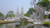 vzor : CHIANG RAI, THAILAND - MAY 9, 2019: Enjoy the garden of White Temple (Wat Rong Khun) with a pond, fountains, bridges, ornate sculptures of Thai mytical creatures, on May 9 in Chiang Rai