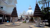 bo : CHIANG RAI, THAILAND - MAY 9, 2019: The carved shrine and prayer trees with numerous metal bo (pho, bodhi) silver leaves, located on the grounds of White Temple (Wat Rongkhun), on May 9 in Chiang Rai Stok Video