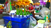 рынок : BANGKOK, THAILAND - APRIL 23, 2019: The vendor of Pak Khlong Talat flower market makes compositions for Buddhist ritual offerings of banana leaves cones and jasmine flowers, on April 23 in Bangkok