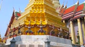 dekor : BANGKOK, THAILAND - MAY 12, 2019: The golden stupa, supported by richly decorated monkeys and demons guard in front of the Royal Pantheon of Grand Palace, on May 12 in Bangkok Stok Video