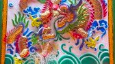 tribunal : BANGKOK, THAILAND - MAY 12, 2019: The stucco panel with relief colorful dragons in front of the fountain in courtyard of Lao Pun Tao Kong Shrine, located in Chinatown, on May 12 in Bangkok