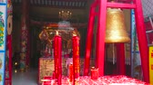 dekor : BANGKOK, THAILAND - MAY 12, 2019: The prayer hall of Chinatowns Lao Pun Tao Kong Shrine with burning candles in front of richly decorated interior, on May 12 in Bangkok Stok Video