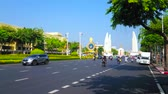dekor : BANGKOK, THAILAND - APRIL 24, 2019: The fast traffic through the Ratchadamnoen Avenue, lined with lush trees, overlooking Democracy Monument on background, on April 24 in Bangkok Stok Video