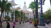 slunečník : CADIZ, SPAIN - SEPTEMBER 19, 2019: The large pedestrian Plaza de San Juan de Dios, the central walking sqaure in old town with Town Hall, palm alley and white sunshades, on September 19 in Cadiz Dostupné videozáznamy