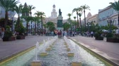 relaxace : CADIZ, SPAIN - SEPTEMBER 19, 2019: Explore San Juan de Dios square with tall palms, plants in pots, fountains, Moret statue, cafes and Town Hall building, on September 19 in Cadiz
