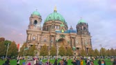 девочки : BERLIN, GERMANY - OCTOBER 3, 2019: The kids jump, trying to catch the large flying bubbles, blown out by the street artisan in Lustgarten Park in front of Berliner Dom, on October 3 in Berlin