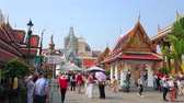 dekor : BANGKOK, THAILAND - MAY 12, 2019: The crowded Grand Palace alley with a view on covered gallery, ornate pavilion and Hor Phra Gandhararat shrine with prang tower, on May 12 in Bangkok Stok Video