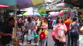 рынок : BANGKOK, THAILAND - MAY 12, 2019: The busy Chinatown market in Mangkon Road; food carts and stalls with sunshades are sandwiched to the buildings and leave only narrow walkway, on May 12 in Bangkok Стоковые видеозаписи