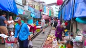 abroncs : MAEKLONG, THAILAND - MAY 13, 2019: Maeklong Railway Market (Talad Rom Hoop) boasts wide range of fresh fruits, vegetables, local foods, snacks and souvenirs, on May 13 in Maeklong