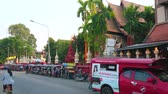 veículo : CHIANG MAI, THAILAND - MAY 2, 2019: The road in front of Wat Phantao Temple with line of parked tuk tuks and driving songtaew pickup truck taxi, on May 2 in Chiang Mai Vídeos