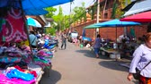 werkkleding : CHIANG MAI, THAILAND - MAY 4, 2019: The busy Pra Pok Clao road with garment and household stalls of chaotic Gate Market, full of porters, bicycles, mopeds and walking people, on May 4 in Chiang Mai Stockvideo