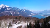 The forests cover the gentle slopes of Zwolferhorn Mount and hide the blue Wolfgangsee lake, seen from cable car, Salzkammergut, St Gilgen, Austria Stock Footage