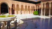 tribunal : GRANADA, SPAIN - SEPTEMBER 25, 2019: Panorama of medieval Court of Lions (Nasrid Palace, Alhambra) with ornate arcade, decorated by pillars and sebka brick carvings, on September 25 in Granada